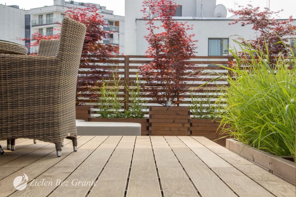 Drewniane donice, panele oraz nawierzchnia ocieplają przestrzeń.